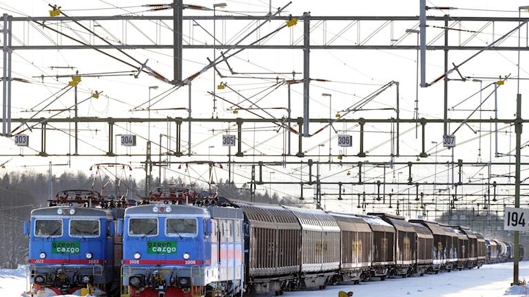 Två godståg på en vintrig bangård.