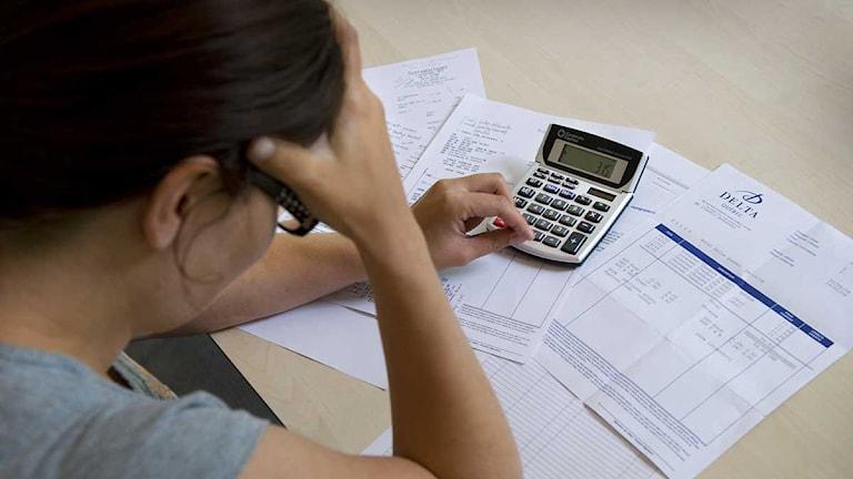 Kvinna betalar räkningar. Foto: Claudio Bresciani/Scanpix