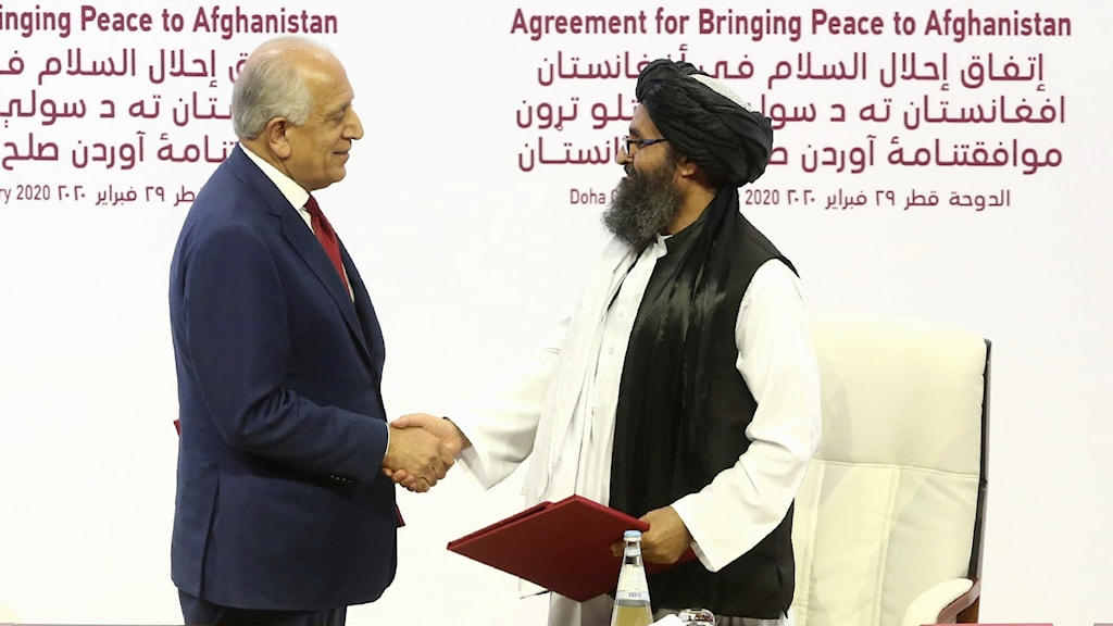 U.S. peace envoy Zalmay Khalilzad, left, and Mullah Abdul Ghani Baradar, the Taliban group's top political leader