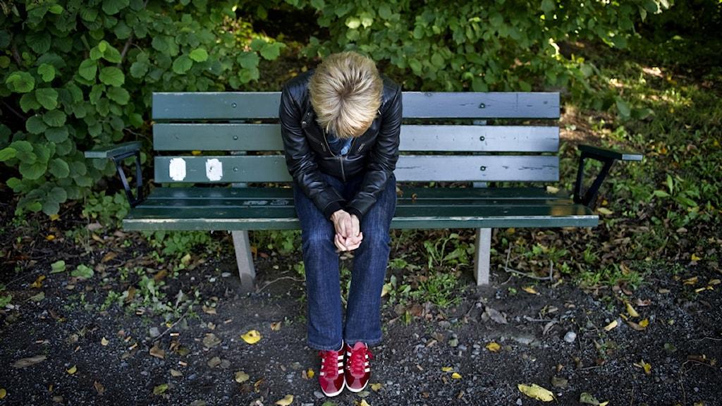 En kvinna sitter på en parkbänk. Foto: Jessica Gow/Scanpix.