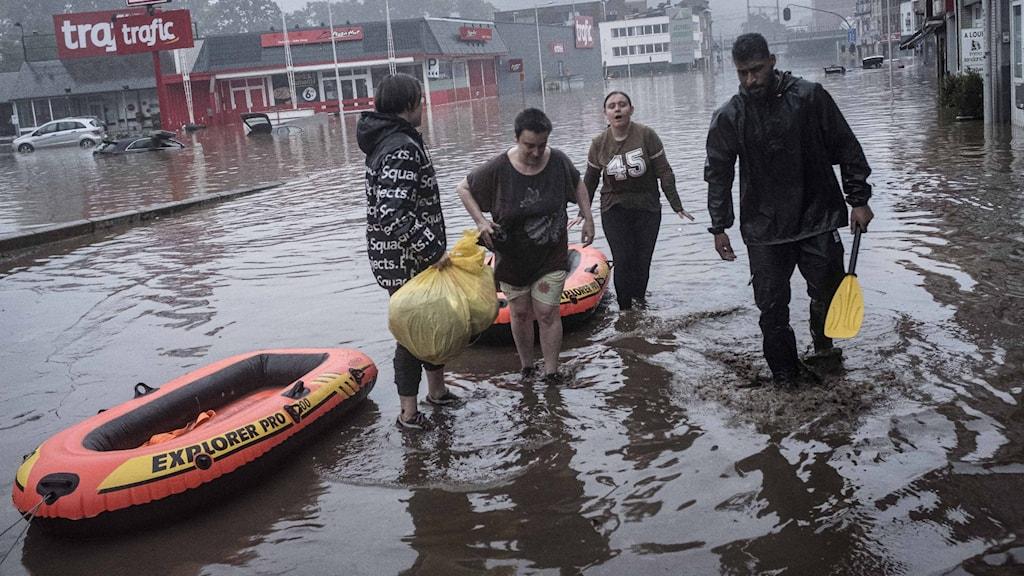 Fyra personer evakueras med gummiflottar från översvämningen i Liege.