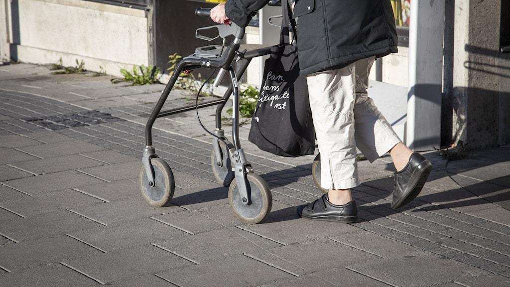 En äldre kvinna med rullator.