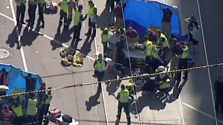 Fotot visar hur flera personer får hjälp av polis och räddningspersonal.