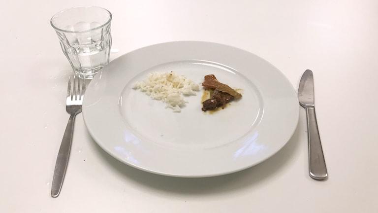 En tallrik med lite ris och kött, bestick samt ett glas med vatten.