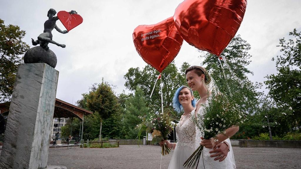 Två nygifta kvinnor med stora hjärtformade ballonger.