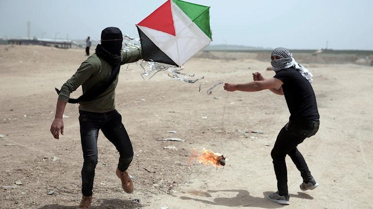 Palestinska demonstranter med en bestyckad drake