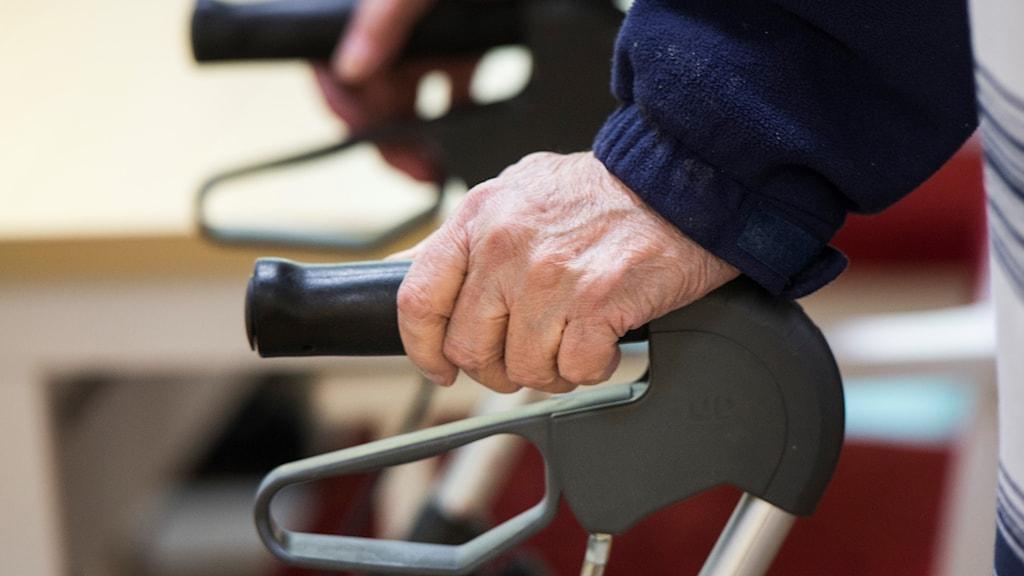 Äldre person med händerna på rollator.