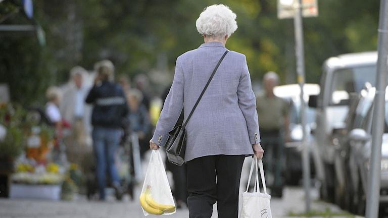 En äldre dam går nerför en gata med en kasse bananer. Arkivfoto: Fredrik Sandberg/Scanpix.