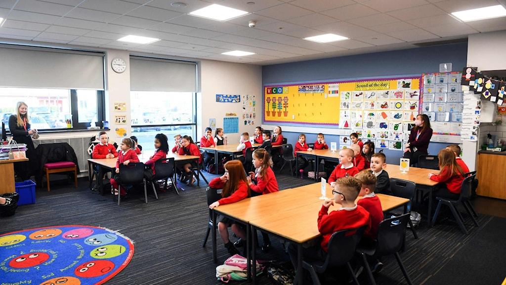 Klassrum med barn i röd skoluniform.