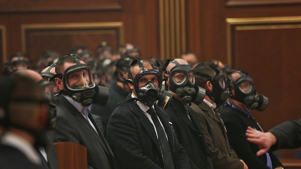 Gasmaskutrustade män inne i Kosovos parlament