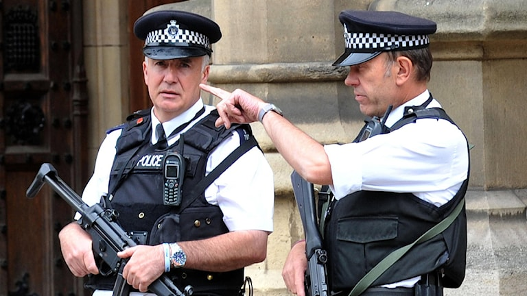 Två brittiska uniformerade polismän står på den avspärrade gatan efter bomhotet som riktades mot huvudstaden London.