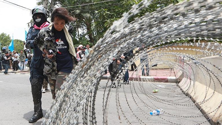 Demonstrant blir bortförd av thailändsk polis.