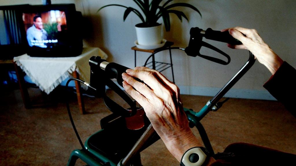 Äldre persons händer på en rullator framför en tv.