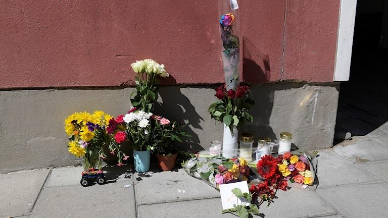 Blommor och kondoleanser utanför den port där en 20-årig man med downs syndrom blev ihjälskjuten.