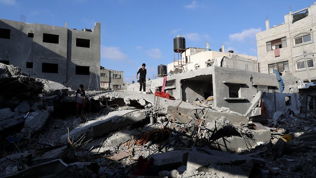 En ung pojke går bland demolerade hus i Gaza.