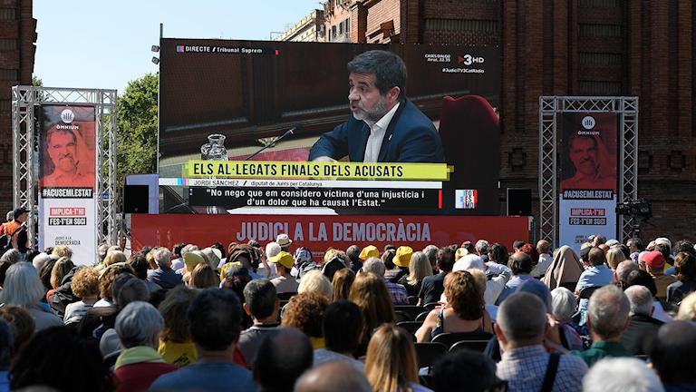 Stor tv-skärm med folkmassa framför.