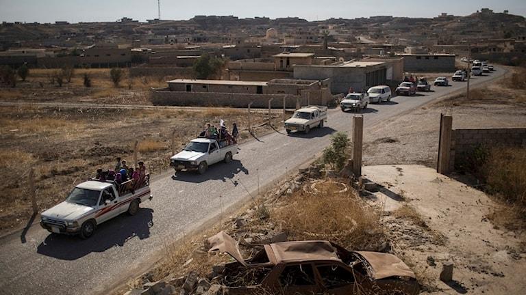 Människor flyr ut ur Mosul i fullastade bilar.