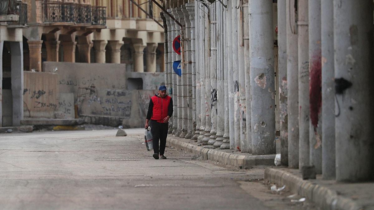 En man på en tom gata i Bagdad.