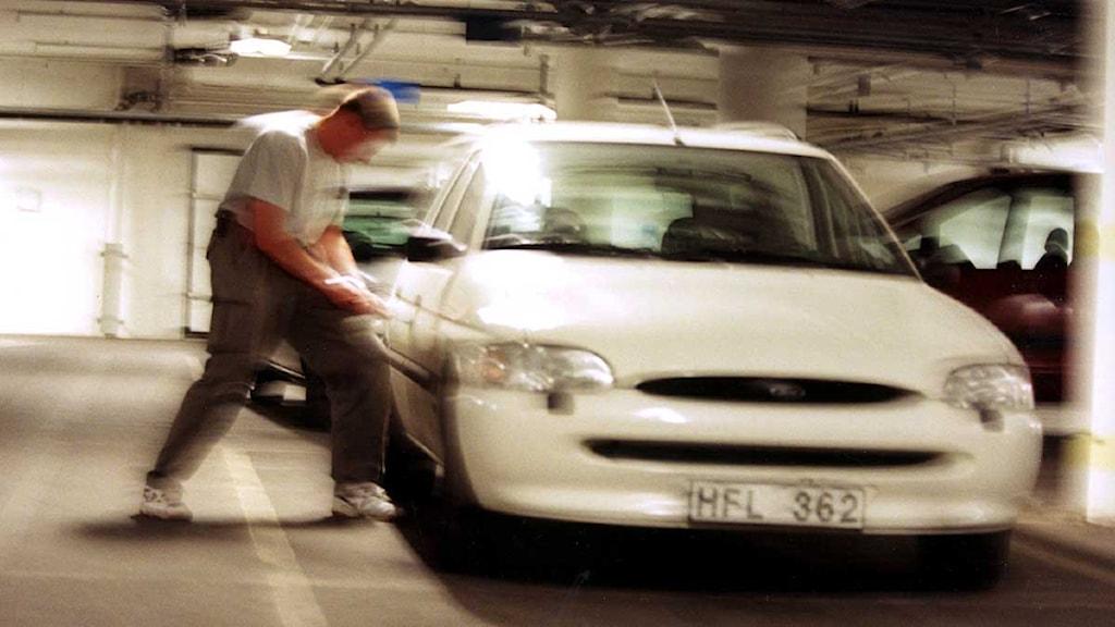 En man bryter sig in i en bil ett garage. Arkivfoto: Rawel Flato/Scanpix.