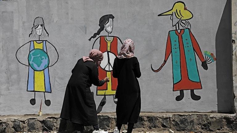 Två kvinnor och en väggmålning.