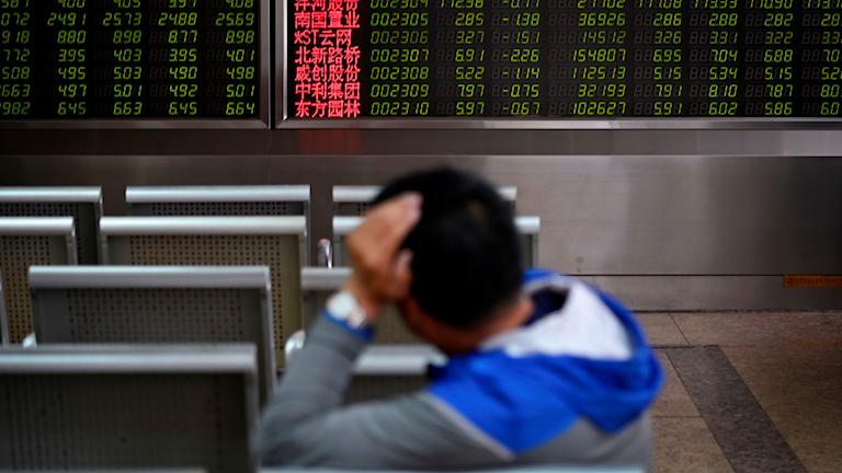 En person tittar på skärmar med kurser på Beijing-börsen