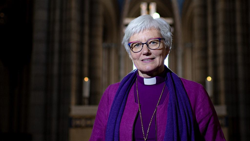 Äldre kvinna i biskopsklädsel i kyrka.