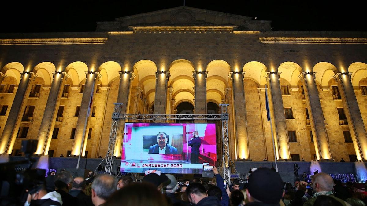Personer tittar på en storbildskärm.