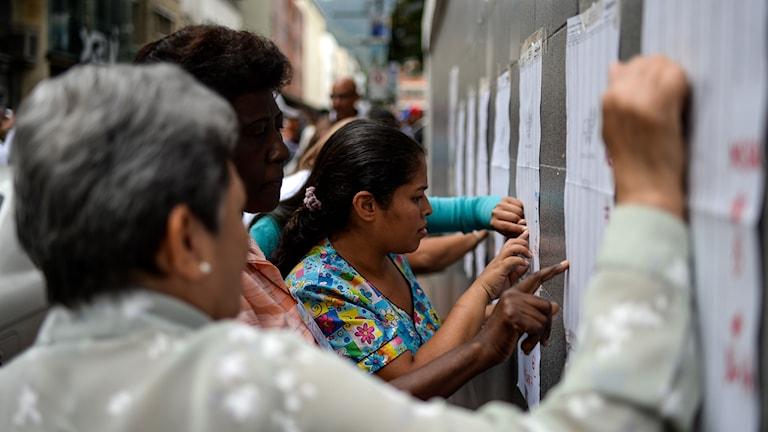 Folk tittar på listor på en vägg
