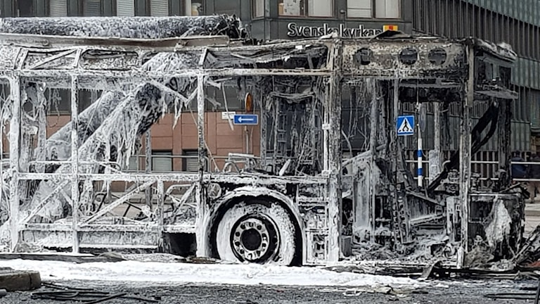 Picture of a bus that has been completely burnt out, leaving only its metal frame.