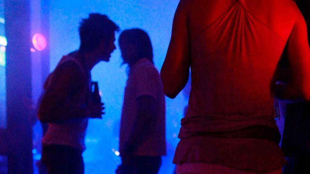 Man står och pratar med en kvinna på en nattklubb, i förgrunden står en person i skenet av rött ljus.