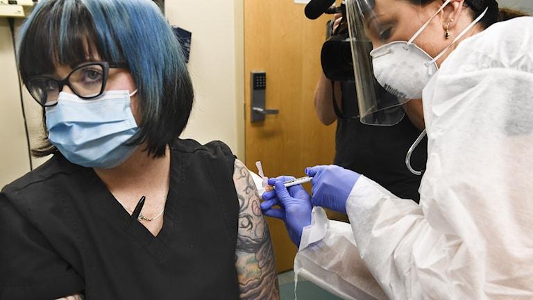 En kvinna vaccineras av en sjuksköterska iklädd munskydd och visir.