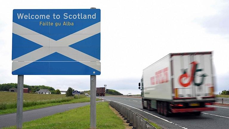 En lastbil passerar en välkomstskylt till Skottland nära gränsen vid Berwick-upon-Tweed.