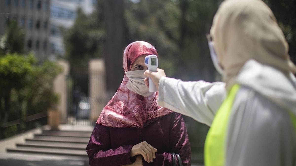 En kvinna i Marocko som får sin temperatur mätt.