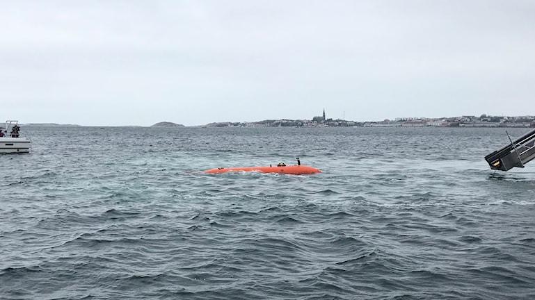 En orange forskningsubåt som är självkörande syns i vattnet