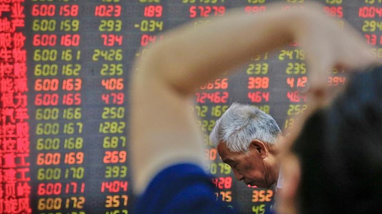 Två kinesiska investerare framför tavla med aktiepriser