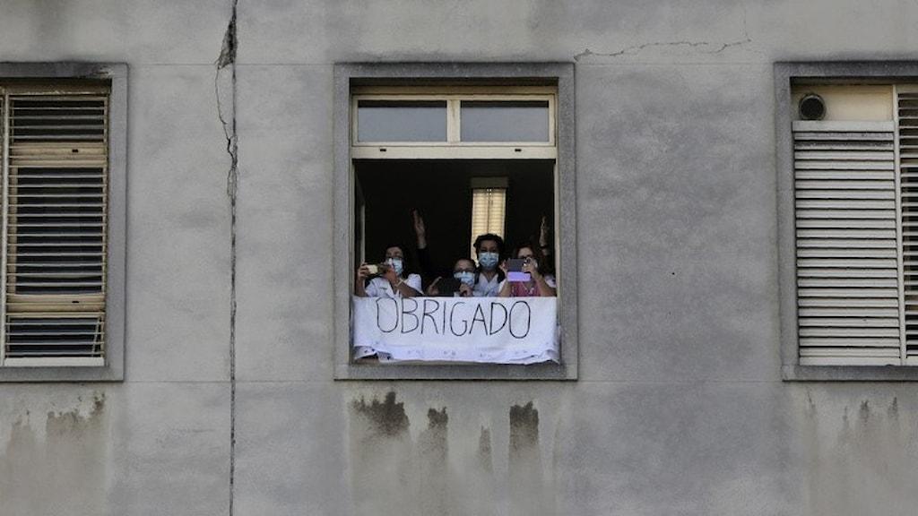 Sjukvårdspersonal som håller upp en banderoll där det står tack på portugisiska.