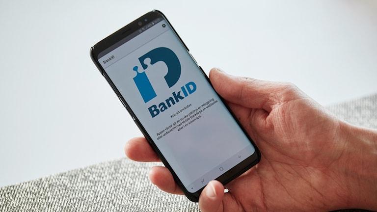 Man håller upp en telefon med Bank-ID appen öppen.