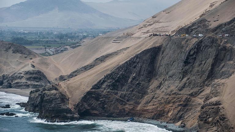 Bussen föll drygt 100 meter ner för klippavsatsen. Bild på lång håll över klippan och vägen.