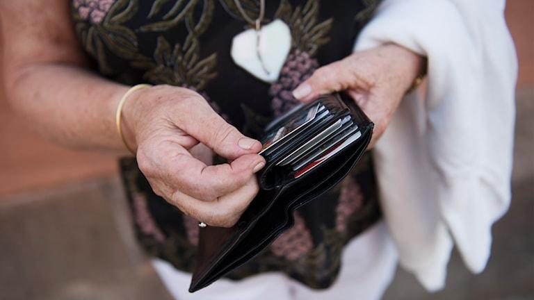 Kvinna håller i en plånbok.