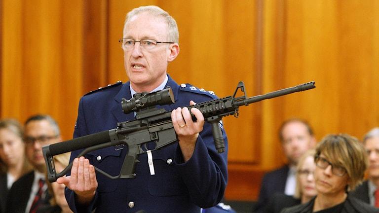 Polisen Mike McIlraith visar den nya nyzeeländska riksdagen en AR-15 under förhandlingarna för striktare vapenlagar.