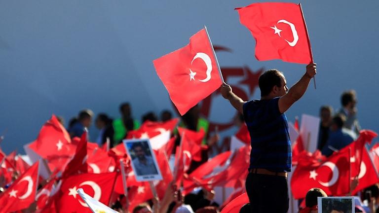 Människor står med turkiska flaggor.