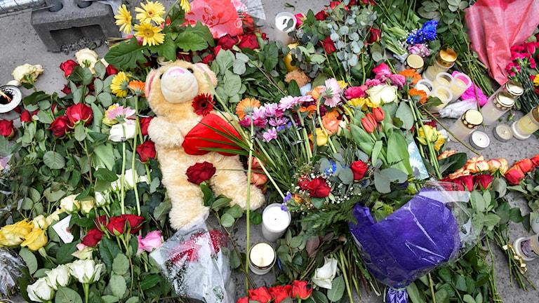 Blommor, ljus och en nalle vid Åhléns i centrala Stockholm.