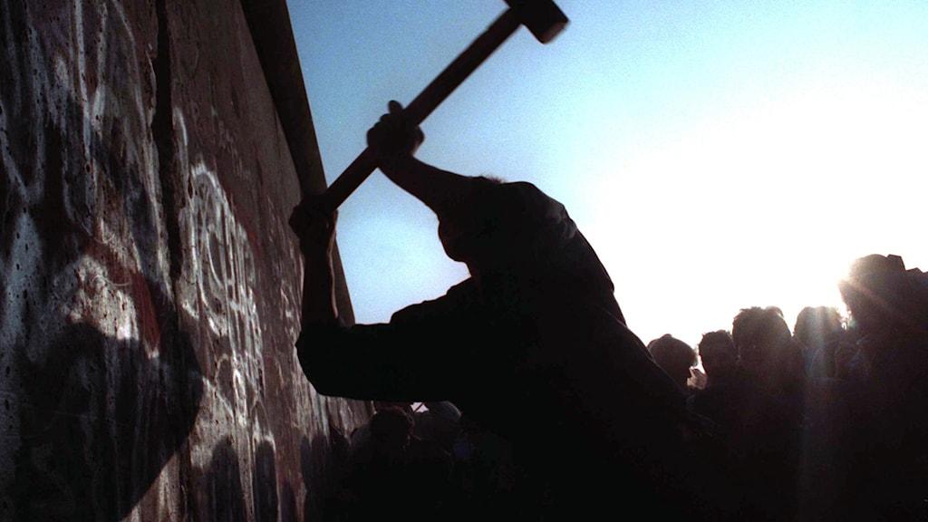 En man hackar på Berlinmuren