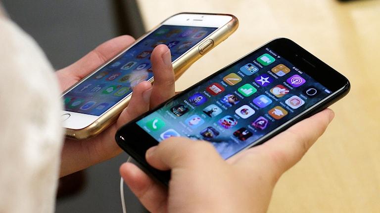 Två telefoner hålls sida vid sida.