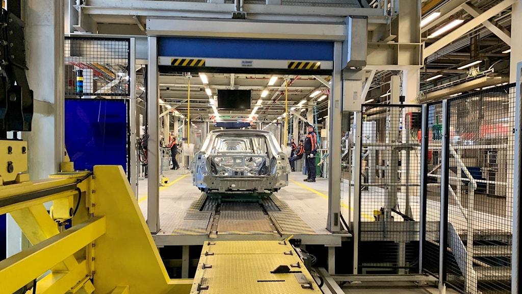Bilproduktion inne hos Volvo Cars. En bilkaross på ett av banden och flera bilbyggare står vid sidan om.