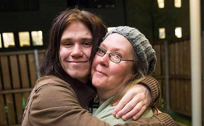 Fotot visar en kille i långt mörkt hår som kramar sin mamma Mona i basker och glasögon.
