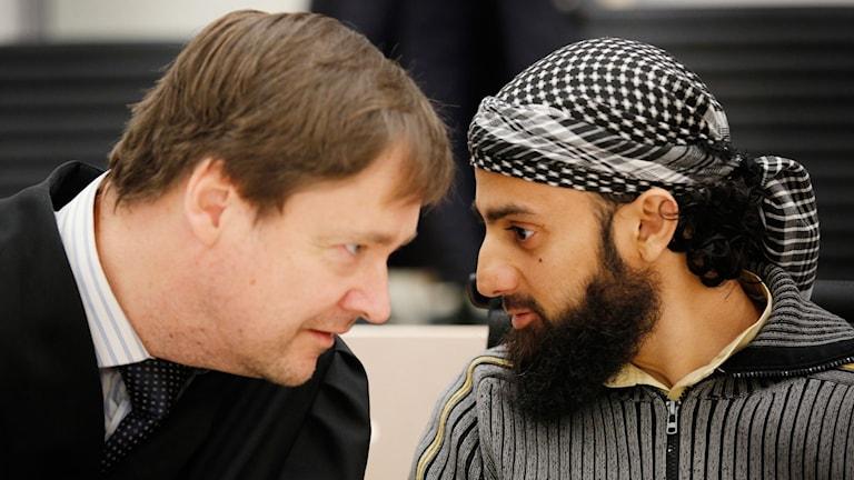 Ubaydullah Hussain pratar med sin försvarsadvokat John Christian Elden.