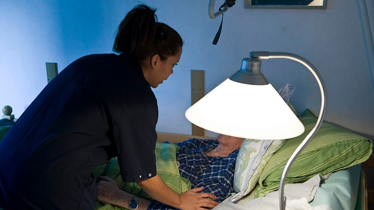 En undersköterska på ett vård- och omsorgsboende hjälper en äldre person som ligger i sängen. Foto: Henrik Montgomery/Scanpix.