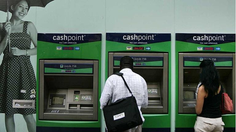 Människor tar ut pengar från bankomater. Foto: Scanpix