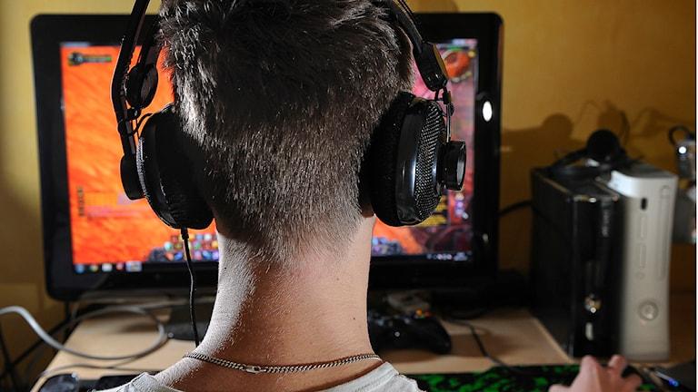 Ung kille med hörlurar sitter framför dator. Foto: Anders Wiklund/Scanpix.